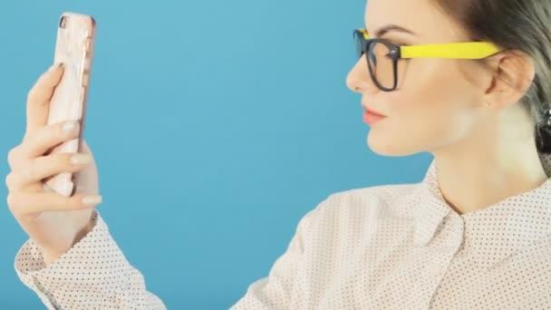 Detailní portrét bruneta pořizování Selfie pomocí Smartphone na modrém pozadí ve studiu. Atraktivní Hipster dívka nosí módní brýle a pomocí její mobilní fotografování sama.