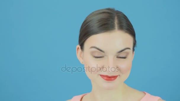 Smějící se žena s dokonalým čerstvé čisté kůže a make-up na modrém pozadí ve studiu. Mládí a koncept péče o pleť