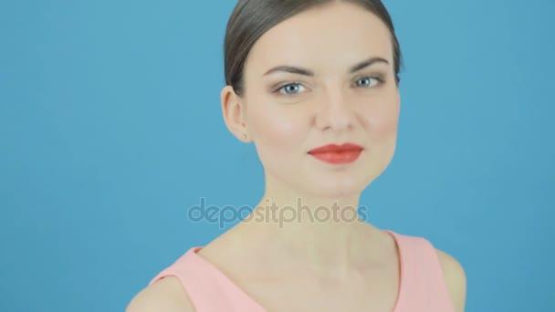 Roztomilá brunetka s dokonalým čerstvé čisté kůže a profesionální make-up na modrém pozadí ve studiu. Mládí a koncept péče o pleť
