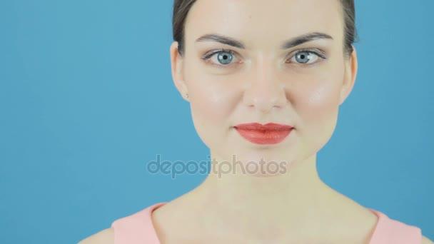 Detailní portrét usmívá krásná žena s dokonalým čerstvé čisté kůže. Mládí a koncepce péče o pokožku. Izolované na modrém pozadí ve studiu