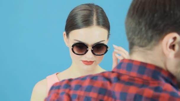 Sada fotek brunetka Model během. Mužské ruky se mění klobouky. Módní portrét Sexy ženy s smyslné rty v červeném klobouku a růžové šaty