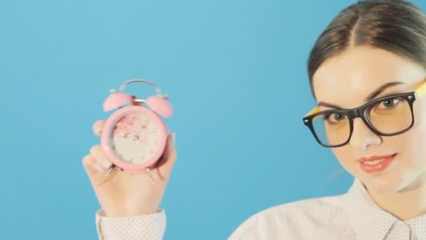 Mladá krásná žena v brýlích a tričko růžové hodiny drží v rukou na světle modrém pozadí ve studiu. Pojem o čase