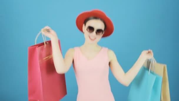 Žena držící hodně barevné tašky. Portrét Roztomilá brunetka s červenou čepici a brýle. Sezónní prodejní koncept.