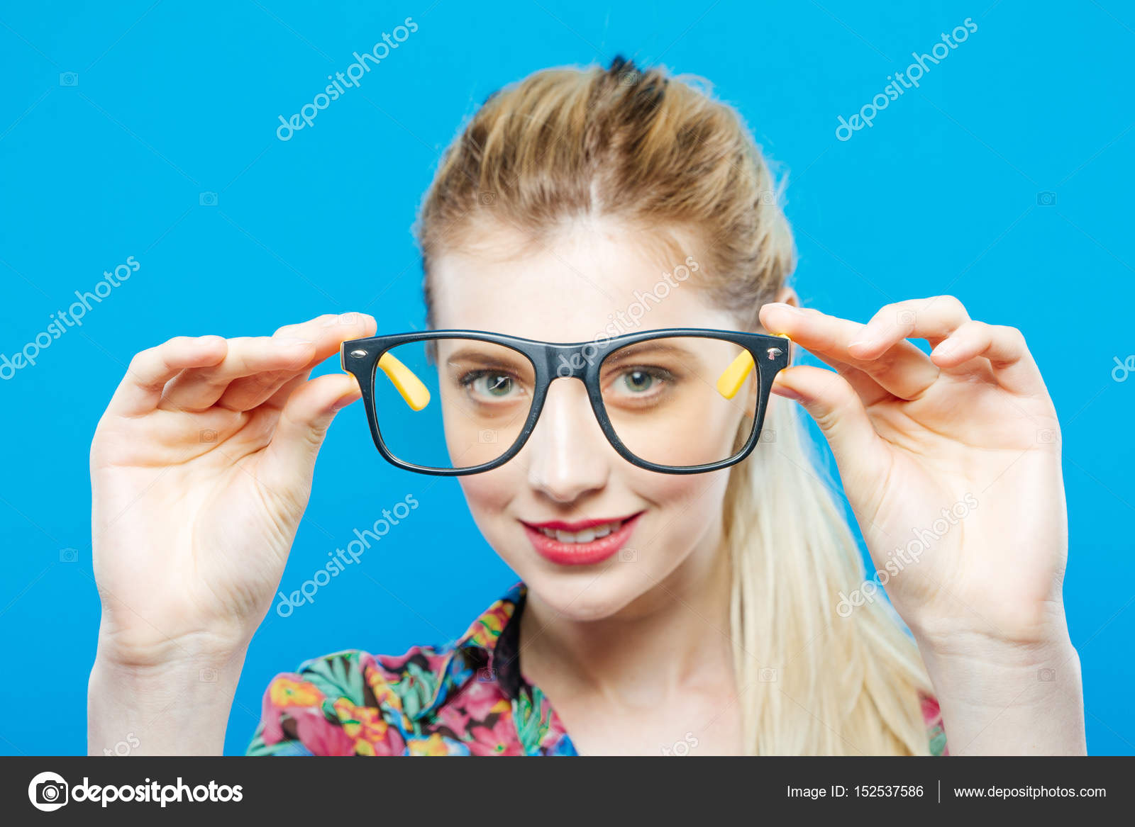 d5516c8dffa Closeup Portrait of Funny Smiling Blonde Woman with Ponytail Wearing  Colorful Shirt and Fashionable Eyeglasses on Blue Background. Sensual Cute  Girl is ...