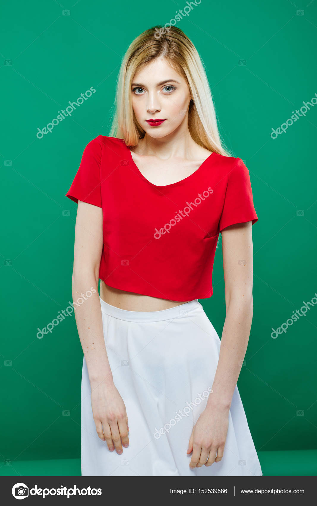 024cdfc0982683 Sexy Young Girl Wearing Red Top and White Skirt is Posing on Green  Background. Portrait