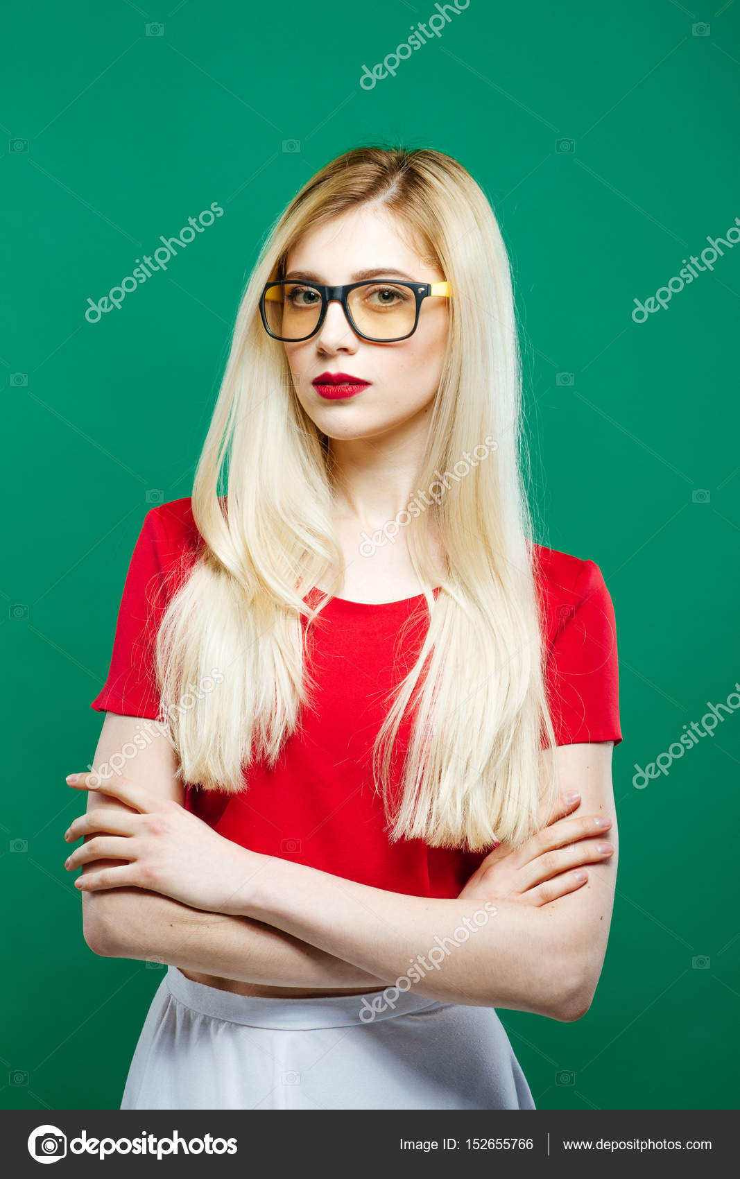 ee3bf4704 Seriuos Girl Wearing Eyeglasses, Red Top and White Skirt on Green  Background. Portrait of Young Woman with Sensual Lips and Long Hair in  Studio.