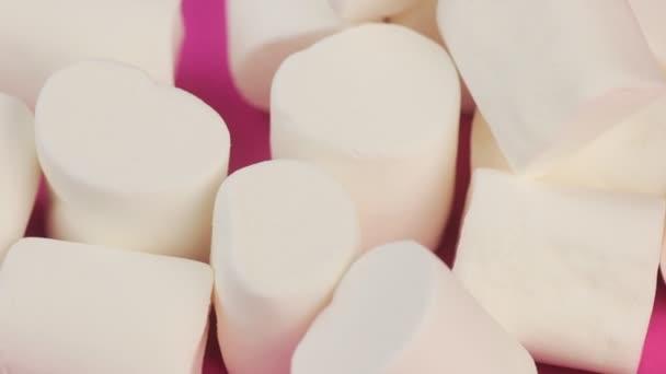 Haldy bílé, měkké, nadýchané Marshmallow na růžovém pozadí. Nezdravé stravovací koncept.