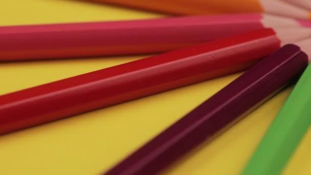 Dřevěné tužky různých barev se nastavují v kruhu na žlutý povrch, barevné umění, jasně červená, zelená, žlutá, růžová, fialová, modrá, zelená. Zblizka, bezešvé smyčka, rotace