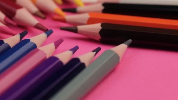 viele verschiedene Buntstifte liegen auf rosa Hintergrund in einer Welle