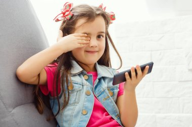 Cute little girl using a smartphone, looking at camera and smiling while on the sofa at home