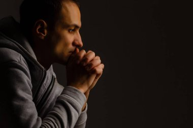 Religious young man praying to God on dark background, black and
