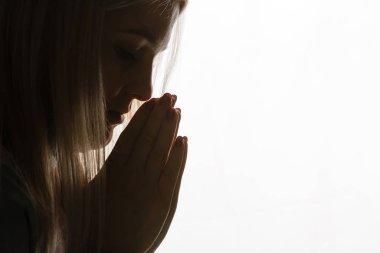 Religious girl praying on background