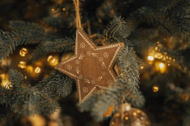 Beautiful  background tree . decorations on a Christmas tree and glare of lights., Xmas Tree Decoration Lights Presents Gifts Toys, Candles And Garland Lighting Indoors. Decorations on a Christmas tree in the form of a star