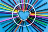 Abstraktní rozostření pozadí. Pastelka srdce - srdce je vyrobeno z barevné tužky