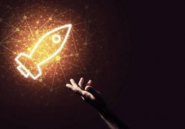 Rocket glowing icon and businessman hand