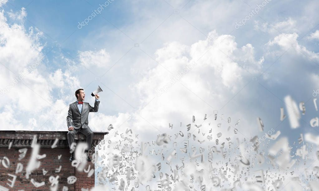 Businessman sitting on house roof