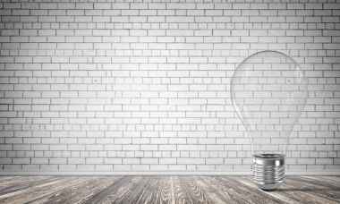 Transparent glass lightbulb in empty room with grey brick wall on background. 3D rendering.