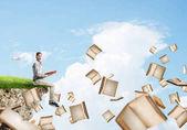 Fotografia Giovane uomo che galleggia sullisola nel cielo blu con il libro rosso nelle mani