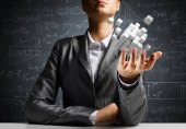 Fotografie Cropped image of business woman in suit presenting multiple cubes in hand as symbol of innovations. Business sketches on background.