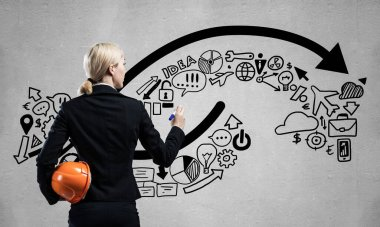 Businesswoman draws arrows consists of business doodles on blackboard. Back view woman with safety helmet and marker pen in hands. Idea generation and business development. Coaching and mentoring.