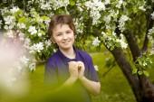 Pěknej kluk kluk v apple zahradní happy s květy na jaře