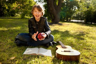 teen boy outdoors with a guitar, a book and an apple on sunset in the park having fun