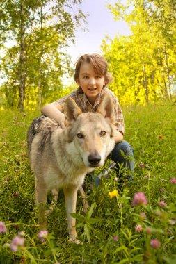 little pretty kid boy with big dog wolf on the grass