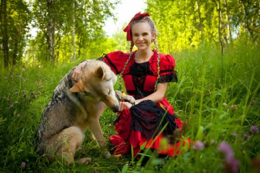 pretty girl weaing red dress sitting with the dog wolf on the grass in the forest