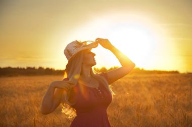 beautiful happy blonde girl with white straw hat standing in the wheat field in the sunset