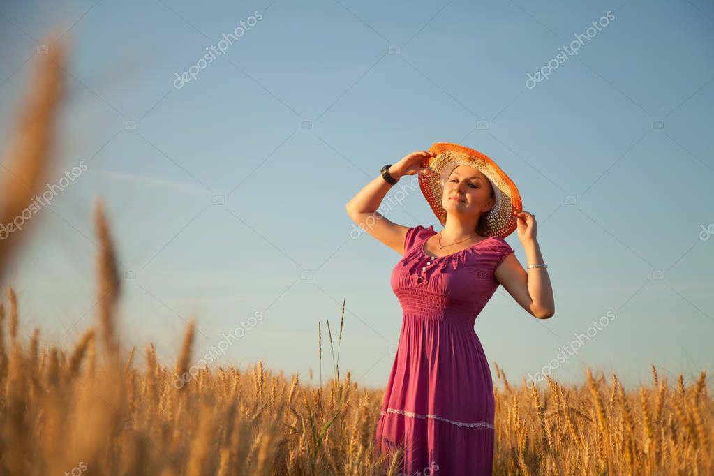 pretty plus size woman with hat standing in the golden wheat field