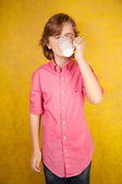 handsome young man with cup of hot drink on yellow bright studio background