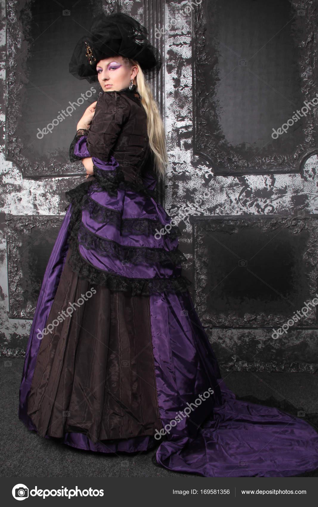 Hübsche blonde Frau trägt historische lila schwarz langes
