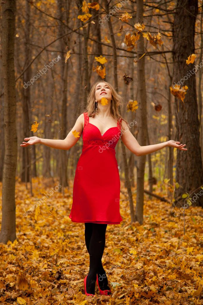 pretty fashionable woman wearing red dress and standing alone in the autumn forest, throwing yellow fall leaves and having fun