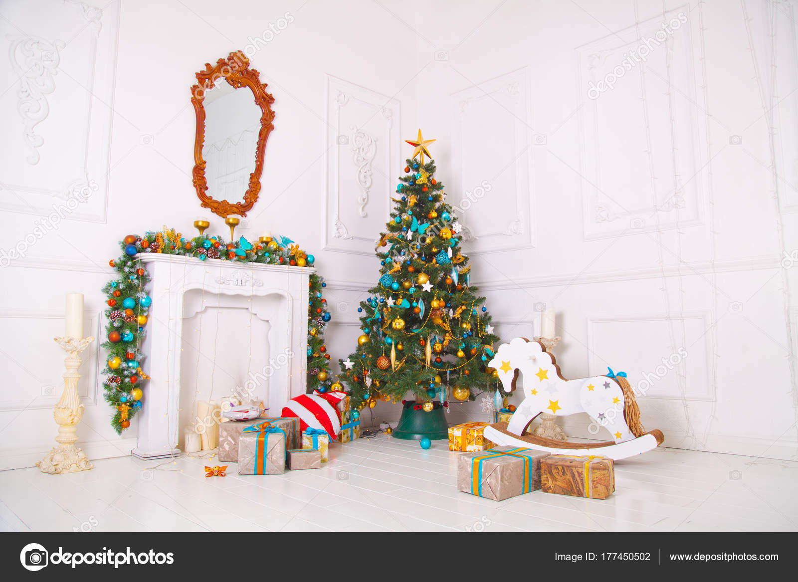 beautiful cozy white room with green christmas tree with blue and golden decorations and presents underneath with beautiful fireplace with candles and toy - Green Christmas Tree With Blue Decorations