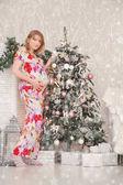 roztomilý těhotná dívka, drželi se za ruce na břiše a pózování doma u vánočního stromu s dárky na bílém pozadí