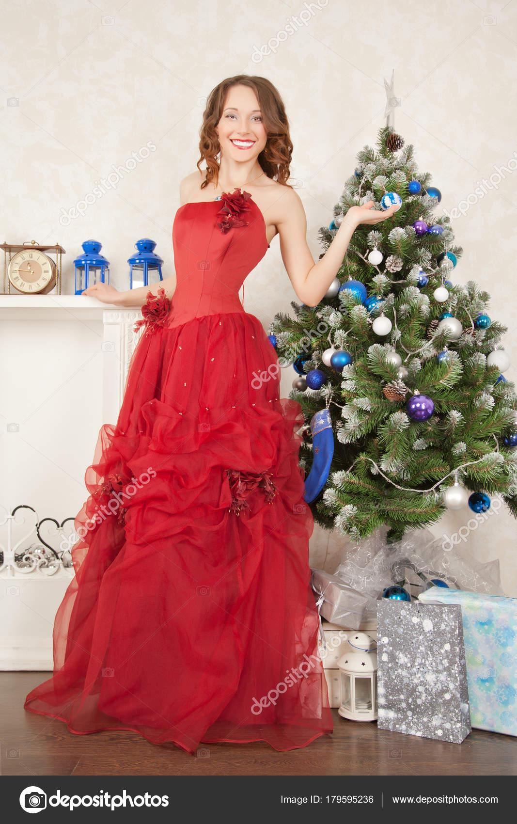 e81b555649 Chica adolescente bastante lindo posando en vestido de noche cerca de un  árbol de Navidad y la chimenea blanca en su casa — Foto de ...