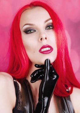 Beautiful alternative slim photomodel with red hair wearing latex rubber black lingerie and posing