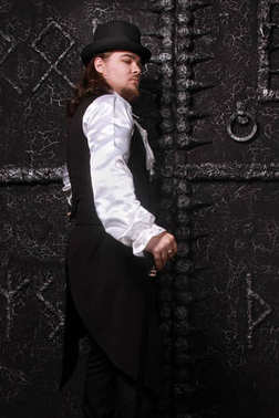 a dangerous warlock in the black historical clothing with a hat and white lace shirt stands in the background of dark black sorcery runic gate
