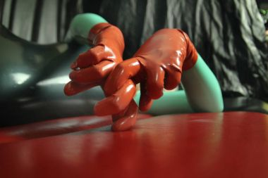 cute short-haired blonde girl posing in latex catsuit and rubber red gloves, alone on a dark background