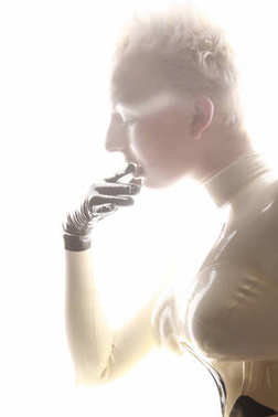 strange futuristic alien albino woman with short blonde hair posing in latex rubber catsuit and tight corset with black gloves on white background isolated