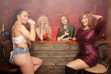 beautiful girls with dogs at a bachelorette party in a red smoky bar drinking alcohol and having fun with white flour
