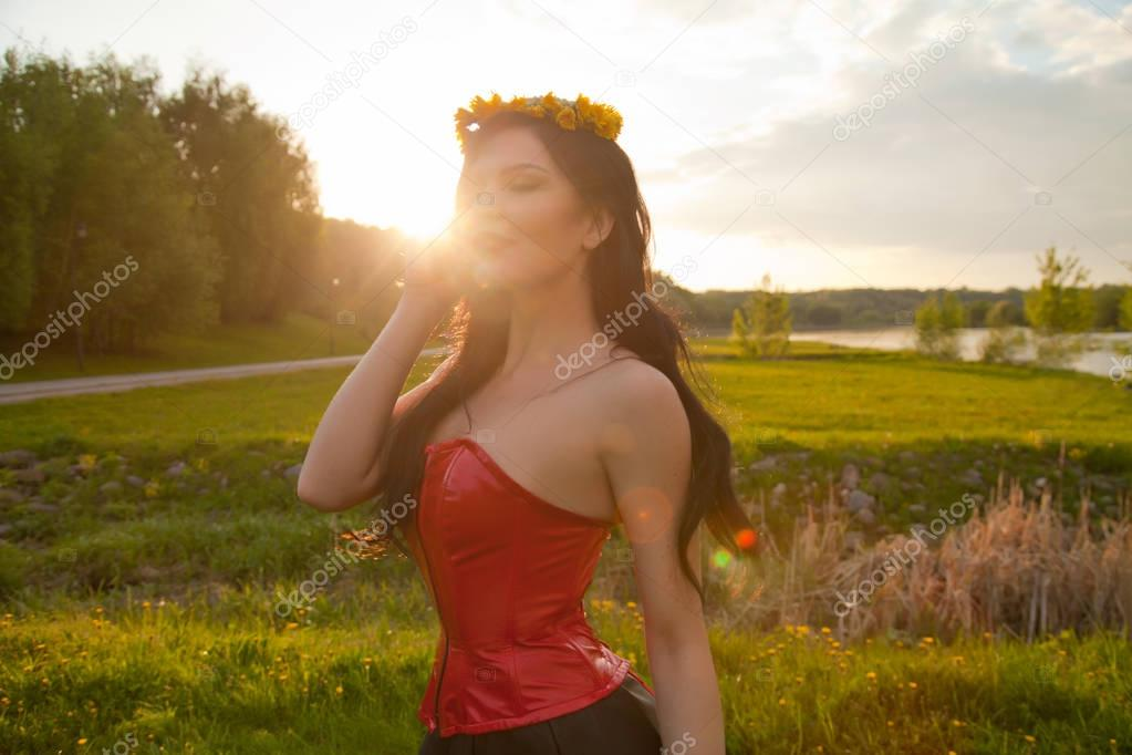 cute young girl with a wreath of yellow dandelions on her head posing in a red corset in the Park at sunset alone