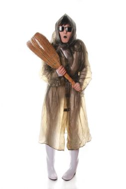 truly strange old lady playing and posing in transparent retro cloak and rubber boots with broom on white background isolated alone