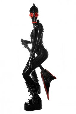 the rock musician woman in a black latex fetish suit and a gas mask stands with fashionable guitar on white background isolated