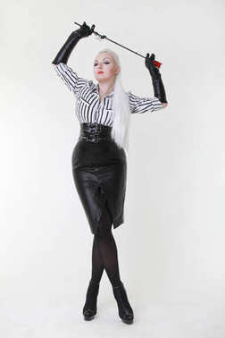 cruel fetish fashion mistress woman standing with bdsm riding crop alone on white background