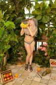 Fotografie süße emotionale junge kurvige platinblonde Mädchen steht in einem Badeanzug mit einem gestreiften Hut und posiert mit vielen Bananen vor einem Hintergrund grüner Pflanzen und Palmen im Gewächshaus