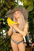 niedliche emotionale junge kurvige Platin Blonde Mädchen stehen in einem Badeanzug mit einem gestreiften Hut und posiert mit viel Bananen auf einem Hintergrund von grünen Pflanzen und Palmen im Gewächshaus