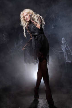 luxurious sweetheart pretty girl with a fluffy white long hair goes in a black lace dress and sheer gloves on a dark background amongst the smoke and lights