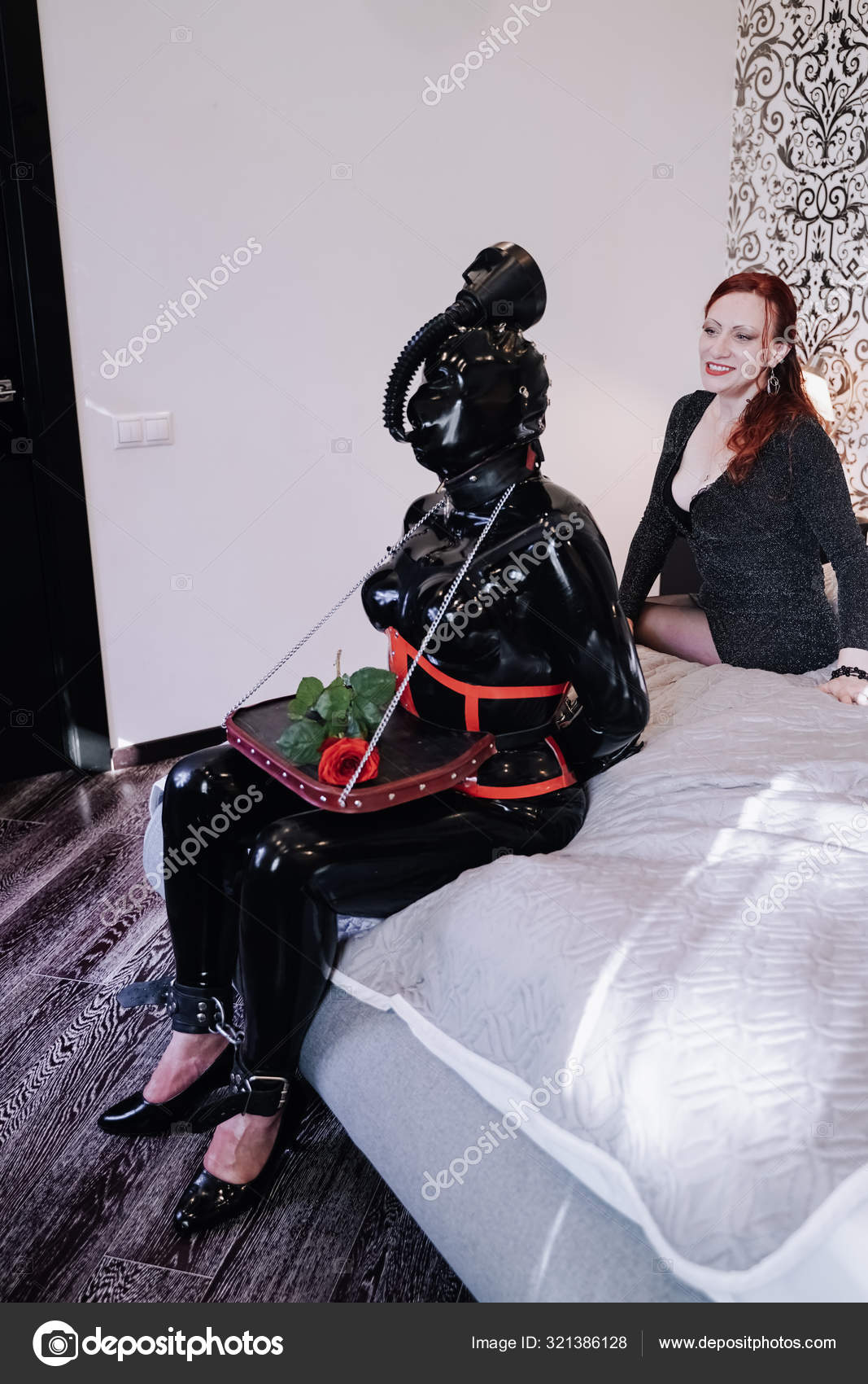 Sexy Frau mit ihrem Latex-Gummisklaven in Maske spielt zu