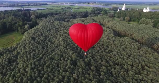 Red hot air balloon in the shape of a heart in the air. View around, aerial.